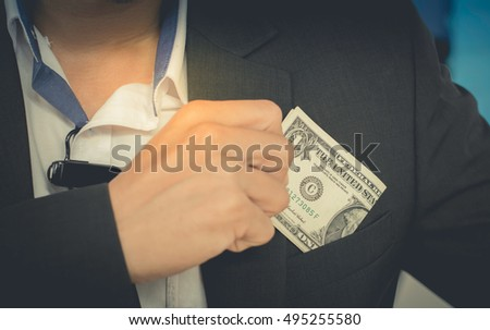 Soft focus businessman with money in office. Currency bribing. businessman hiding money in jacket pocket. Corruption and fraud concepts.