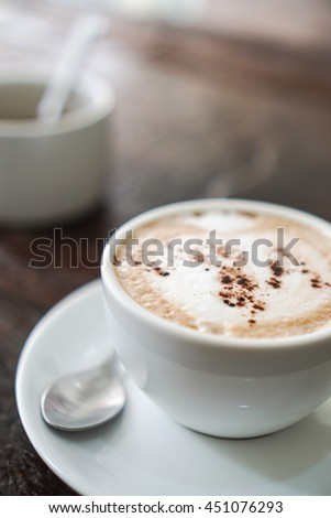 Soft focus cappuccino coffee on wood table and cup of sugar background