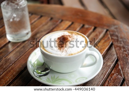 Soft focus cappuccino coffee on wood table and water background