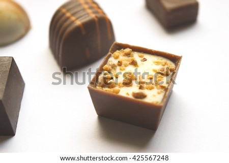 Soft focus chocolate candies on white background. Sweet chocolate pralines with nuts almonds and cream. Milk chocolate praline on white. Variety of sweet tasty candies. Chocolate candy background. - stock photo