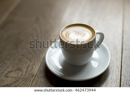 Soft focus coffee macchiato on wood table in the mornong mood and tone.