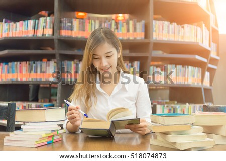 Soft focus female student reading book in a high school library. Blurred background.