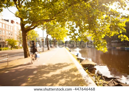 Soft focus image. Beautiful street view of  boats parked along the banks of canal. Women cycling home after the work day.
