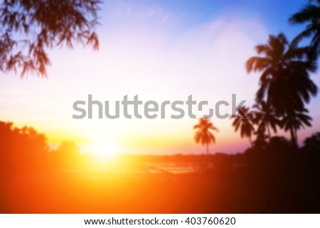 Soft focus image field during sunrise. Abstract blur colorful background of blurred colorful rays light sky clouds with silhouette coconut tree vacation summer. Purple Nature wallpaper of sunset. - stock photo