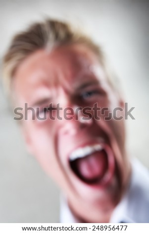 Soft focus image of a yelling man.
