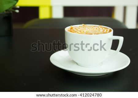 Soft focus of A Latte Coffee art on the black desk. - stock photo