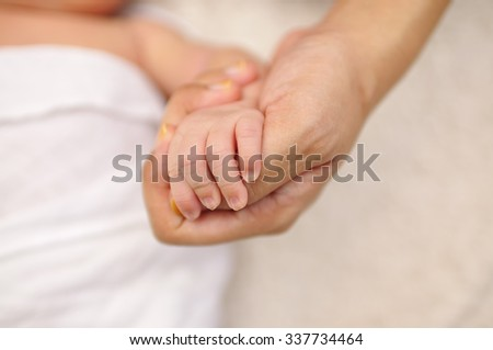 Soft Focus of Close up Mother hand hold Baby Hands,  Loving Concept and selective Focus