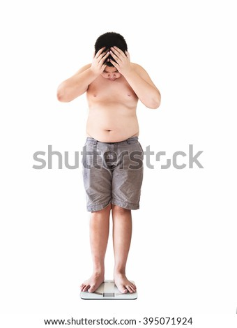 Soft focus of fat boy disappoint his fatness while standing on weighing machine over white background - stock photo