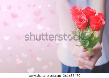 Soft focus of Hand holding bouquet a red roses with abstract blurred free space background. Happy valentine's day concept. Pink and white heart bokeh. - stock photo