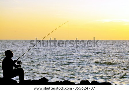 soft focus of silhouette of angler fishing on the rock at the beach of malacca straits.