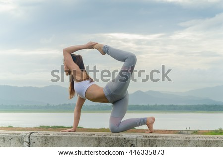 Soft focus of young woman practicing yoga on the cement barrier in the morning.