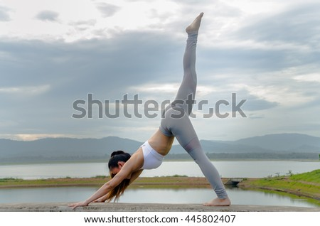 Soft focus of young woman practicing yoga on the concrete barrier in the morning.