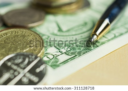 Soft focus on pen with blur coins on bank note background