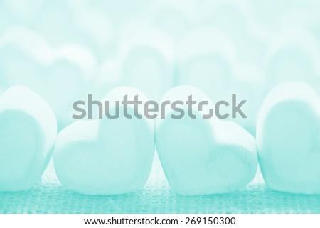Soft focus pastel color marshmallows on burlap background - stock photo