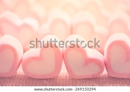 Soft focus pink and white marshmallows on burlap background - stock photo