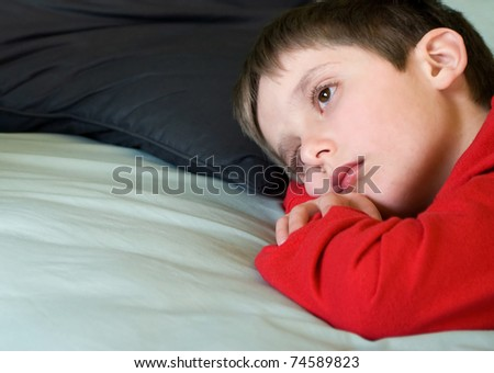 soft focus portrait of a young boy laying on his bed with a sad and thoughtful expression, copy space at left
