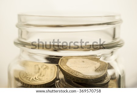 Soft focus stack of coins in glass jars  - stock photo