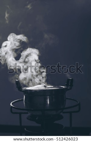 Soft focus steam over cooking pot in the dark