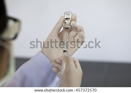 Soft focus vial and blurred syringe on hand of a nurse,doctor administer the injection (Vaccine, drugs, medication, fluid) in color tone in the hospital. - stock photo