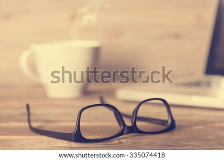 Soft focus wooden work table with glasses, laptop, cup of hot coffee, in dramatic light vintage toned. - stock photo
