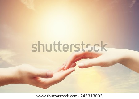 Soft, gentle touch of man and woman against sunny sky with flare in vintage mood. Love, connection, help concepts.