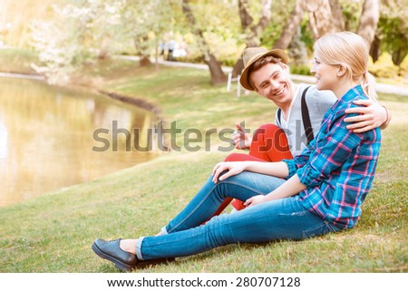Soft glance. Sweet lovely couple sitting on grass in park and embracing each other. - stock photo