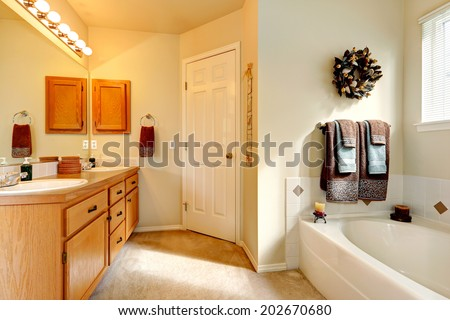 Soft ivory bathroom with carpet floor and white bath tub. View of honey bathroom vanity cabinet with mirror