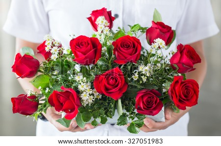 soft light tone with male hand giving bouquet of red roses