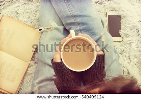 Soft photo of girl On shaggy rug with old book and cup of tea in hands.Top view