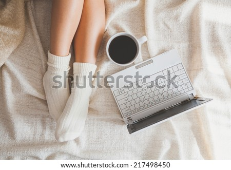 Soft photo of woman on the bed with notebook and cup of coffee, top view point - stock photo