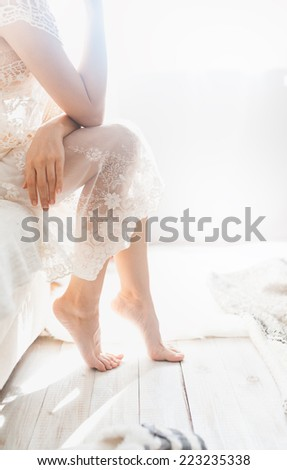 Soft photo of woman on the bed with sunlight from window in bright white room - stock photo