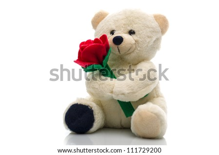 Soft plush teddy bear toy clutching a single red rose in its arms for an anniversary or Valentines celebration - stock photo