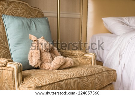 Soft plush toy bunny on a chair in a hotel room - stock photo