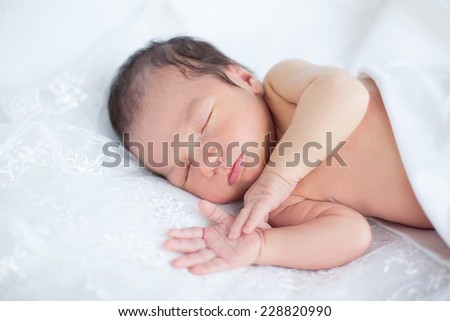 Soft portrait of newborn baby boy kid on white lace background. Focus on close eye and lips - stock photo