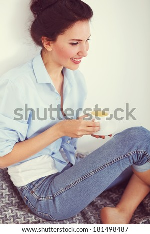 Soft portrait of teenage girl drinking hot tea at home