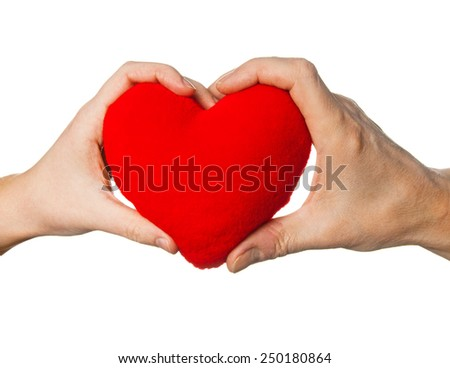 Soft red heart in woman and man hands - stock photo