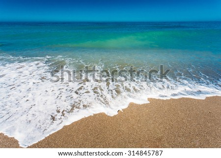 Soft Sea Ocean Waves Wash Over Golden Sand Background. Wave of the sea on the sand beach.