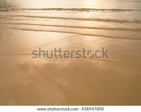 Soft sea wave sand beach at sunset / sunrise. Orange color of sea water surface reflect with sunset. Summer an recreation concept. - stock photo