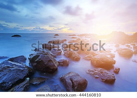 Soft setting sun and wave with sunset over sea and rocks coast - stock photo