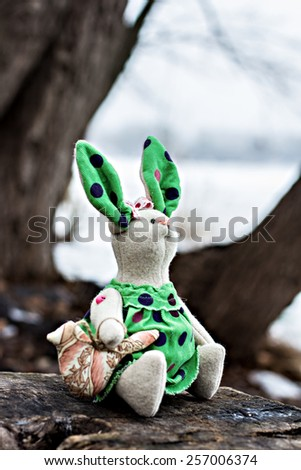 Soft toy - bunny sitting on an old tree. - stock photo