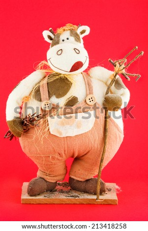 Soft toy. The cow with stick in its hand isolated on red background
