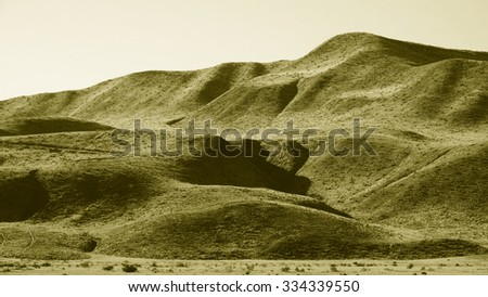 Soft undulating forms and dry grass mark the foothills of the southern Sierra Nevada range in Central California. (Duotone image)