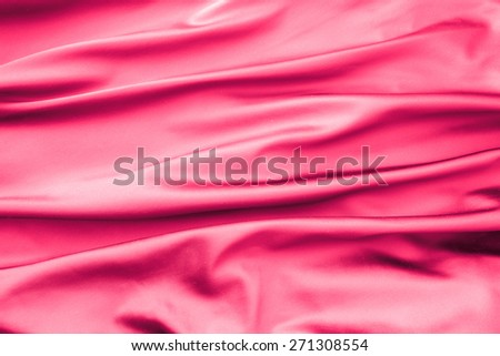 Soft velvet piece of pink fabric with folds to be used as background - stock photo