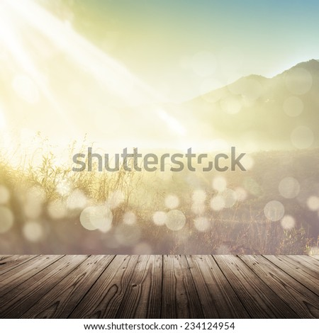 Soft vintage defocused spring background with wooden table sunshine and bokeh over grass - stock photo