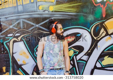 Soft vintage photo of cool bearded man,posing next to the wall in the city street,laughing and having fun,listen his favorite music on earphones.mans fashion,round sunglasses,hight fashion look - stock photo