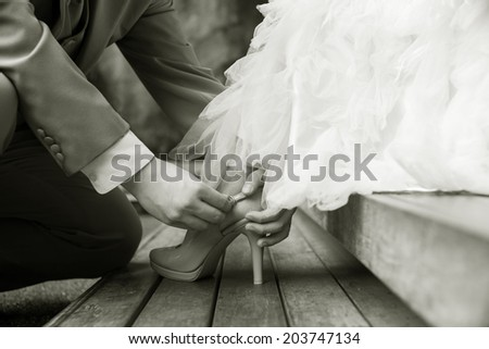 soft vintage sepia tone image of groom assisting bride putting on her shoes - stock photo