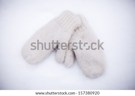 Soft, warm, knitted mittens on the white snow - stock photo