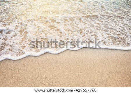 Soft Wave Of Ocean On Sandy Beach At Warm Gold Sunset Light. Background. Selective focus. - stock photo