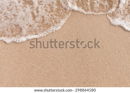 Soft wave of sea on sandy beach - stock photo