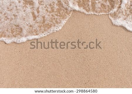 Soft wave of sea on sandy beach - stock photo